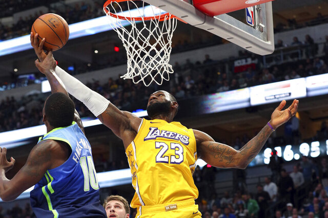Dallas Mavericks forward Dorian Finney-Smith (10) tries to defend against a shot by Los Angeles Lakers forward LeBron James (23) during the second half of an NBA basketball game Friday, Jan. 10, 2020, in Dallas. (AP Photo/Richard W. Rodriguez)