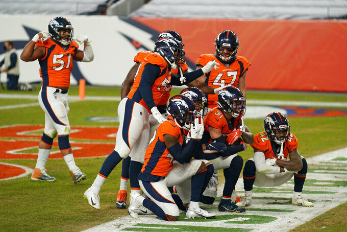 Denver Broncos celebrate after free safety Justin Simmons (31) made an interception against the Las Vegas Raiders during the second half of an NFL football game, Sunday, Jan. 3, 2021, in Denver. (AP Photo/Jack Dempsey)
