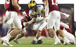 Michigan's Blake Corum (2) carries the ball against Nebraska's Nick Henrich (42) during the first half of an NCAA college football game Saturday, Oct. 9, 2021, at Memorial Stadium in Lincoln, Neb. (AP Photo/Rebecca S. Gratz)