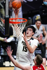 Purdue center Zach Edey (15) shoots over Wisconsin forward Micah Potter (11) during the second half of an NCAA college basketball game in West Lafayette, Ind., Tuesday, March 2, 2021. (AP Photo/Michael Conroy)