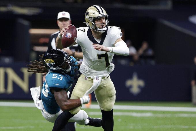 New Orleans Saints quarterback Taysom Hill passes under pressure from Jacksonville Jaguars linebacker Dakota Allen (53) in the first half of an NFL preseason football game in New Orleans, Monday, Aug. 23, 2021. (AP Photo/Derick Hingle)