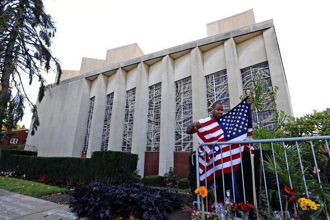 A man places an American flag outside the Tree of Life synagogue in Pittsburgh on Sunday, Oct. 27, 2019, the first anniversary of the shooting at the synagogue that killed 11 worshippers. (AP Photo/Gene J. Puskar)