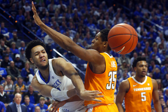 Kentucky's EJ Montgomery, left, passes the ball away from Tennessee's Yves Pons (35) during the first half of an NCAA college basketball game, Tuesday, March 3, 2020, in Lexington, Ky. (AP Photo/James Crisp)
