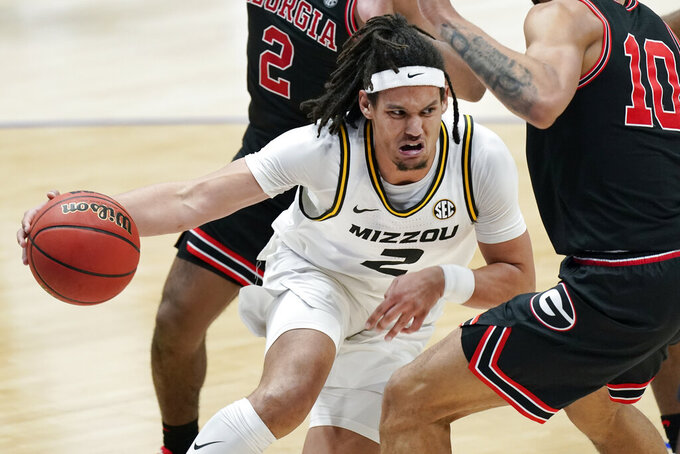 Missouri's Drew Buggs (2) tries to drive through Georgia defenders in the second half of an NCAA college basketball game in the Southeastern Conference Tournament Thursday, March 11, 2021, in Nashville, Tenn. (AP Photo/Mark Humphrey)