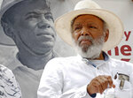 FILE- In this June 26, 2016, photo, civil rights activist James Meredith sits in front of a 1966 photograph of himself during a commemoration of the 50th anniversary of his 1966 March Against Fear at the Capitol in Jackson, Miss.