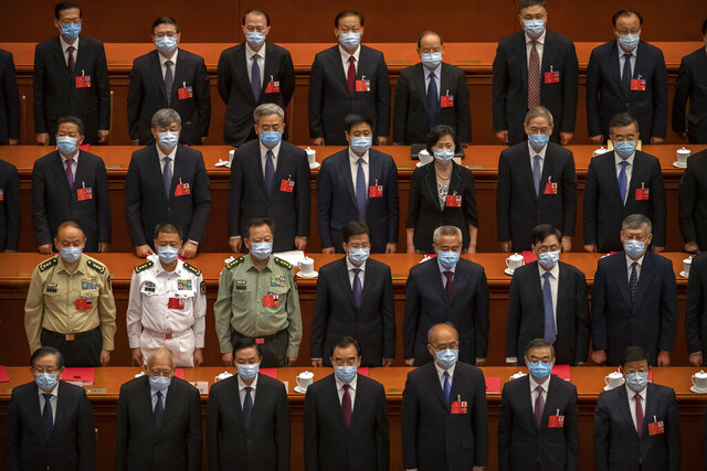 Delegates stand during the closing session of China's National People's Congress (NPC) in Beijing, Thursday, May 28, 2020. China's ceremonial legislature has endorsed a national security law for Hong Kong that has strained relations with the United States and Britain. (AP Photo/Mark Schiefelbein)