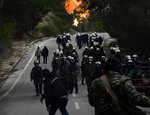 A protester throws a petrol bomb against riot police during clashes in Diavolorema near the area where the government plans to build a new migrant detention center, on the northeastern Aegean island of Lesbos, Greece, Wednesday, Feb. 26, 2020. Local authorities declared a 24-hour strike on two eastern Greek islands Wednesday to protest government plans to build new migrant detention camps there. (AP Photo/Michael Varaklas)