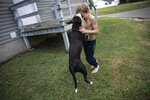 Donovyn Bonice, 8, plays with his dog, Delilah, on his family's back porch in Bidwell, Ohio, on Monday, July 27, 2020. His mother, Tasha Lamm, 30, is raising her two sons on public assistance. (AP Photo/Wong Maye-E)
