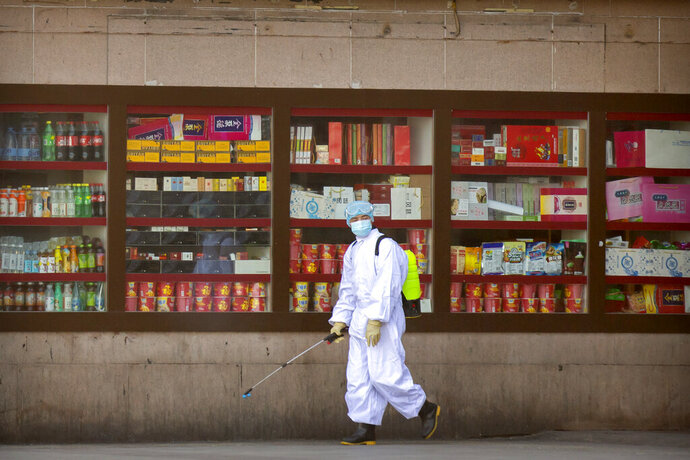 A worker sprays disinfectant outside the Beijing Railway Station in Beijing, Saturday, Feb. 15, 2020. People returning to Beijing will now have to isolate themselves either at home or in a concentrated area for medical observation, said a notice from the Chinese capital's prevention and control work group published by state media late Friday. (AP Photo/Mark Schiefelbein)