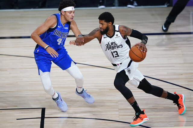 Los Angeles Clippers' Paul George (13) drives to the basket against Dallas Mavericks' Justin Jackson (44) during the second half of an NBA basketball first round playoff game Tuesday, Aug. 25, 2020, in Lake Buena Vista, Fla. (AP Photo/Ashley Landis, Pool)