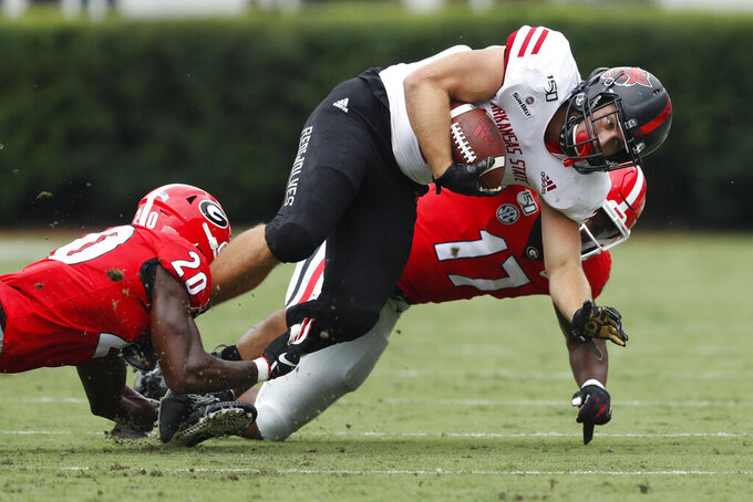Arkansas State running back Ryan Graham (18) is brought down by Georgia defenders J.R. Reed (20) and Nakobe Dean (17) In the first half of an NCAA college football game Saturday, Sept. 14, 2019, in Athens, Ga. (AP Photo/John Bazemore)