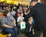 Actor Alec Baldwin looks at a sign made by 10-year-old Lily Tipling during his visit to the Leeland Station Clubhouse in Stafford County, Va., on Tuesday, Oct. 22, 2019. Baldwin encouraged the youngster to run for the White House in 25 years. The actor campaigned Tuesday for Democratic legislative candidates in a Virginia election that is viewed as a warmup to the 2020 presidential contest. (Peter Cihelka/The Free Lance-Star via AP)