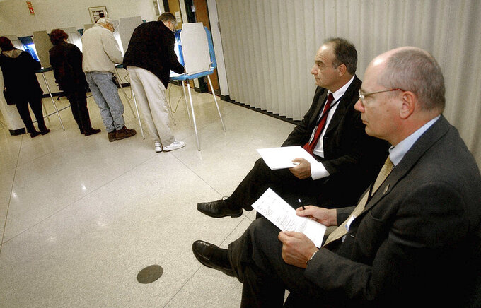 FILE - In this Nov. 2, 2004, file photo, parliamentarians Goran Lennmarker, right, of Sweden and Stavros Evagorow, of Cyprus, observe the American voting process as voters cast their ballots at Robbinsdale City Hall in Robbinsdale, Minn. The two men are members of the Organization for Security and Cooperation in Europe. Officials said Friday, Sept. 18, 2020, that due to the coronavirus pandemic, the security organization had drastically scaled back plans to send up to 500 observers to the U.S. to monitor the Nov. 3 presidential election, and now will deploy just 30. (AP Photo/Jim Mone, File)