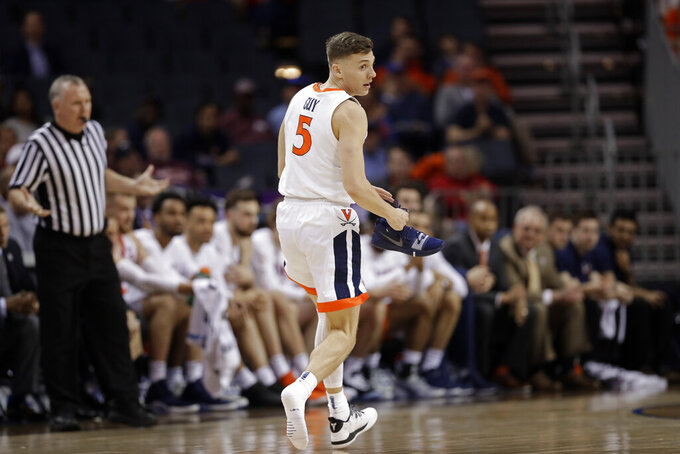 Virginia's Kyle Guy (5) holds his shoe as he runs down the court during the first half of an NCAA college basketball game against North Carolina State in the Atlantic Coast Conference tournament in Charlotte, N.C., Thursday, March 14, 2019. (AP Photo/Chuck Burton)