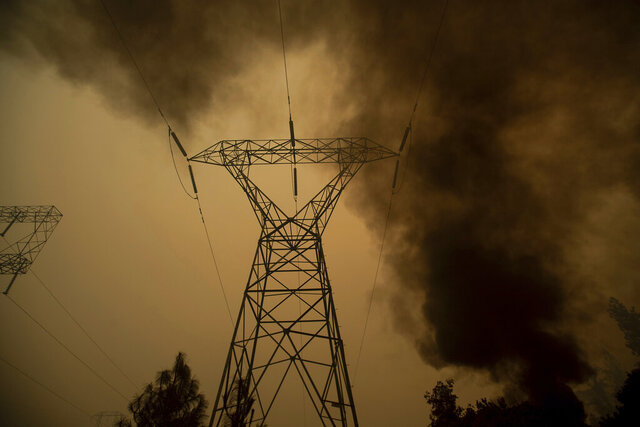 FILE - In this Nov. 9, 2018, file photo, smoke billows around power transmission lines as the Camp Fire burns in Big Bend, Calif. Pacific Gas & Electric Co., the nation's largest electric utility, filed for bankruptcy last year after facing an estimated $50 billion in damages from several Northern California wildfires that were linked to its equipment, including one blaze in 2018 that killed 85 people and destroyed about 19,000 buildings. (AP Photo/Noah Berger, File)