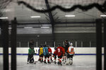 In this Feb. 21, 2019 photo Malakye Johnson (1) gathers with his teammates during a Snider Hockey practice at the Scanlon Ice Rink in Philadelphia. (AP Photo/Matt Rourke)