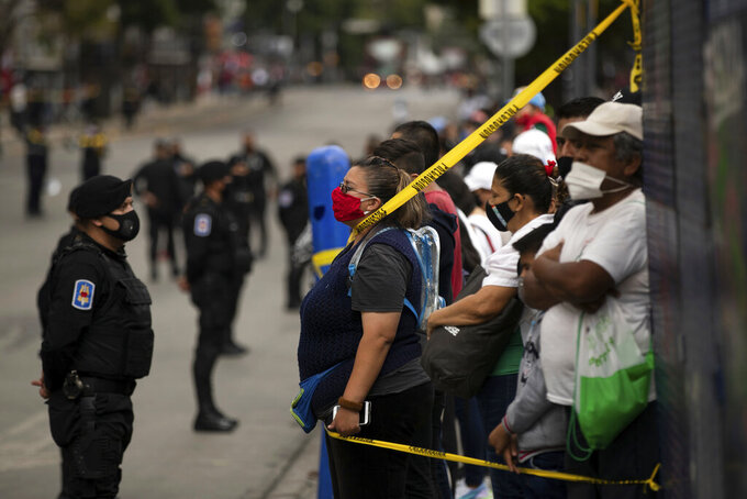 Spectators take position near the perimeter to where the annual Independence Day military parade will pass on Mexico City's Juarez Avenue, Wednesday, Sept. 16, 2020. Mexico celebrates the anniversary of its independence uprising of 1810. (AP Photo/Fernando Llano)