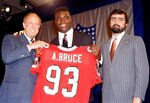 FILE - In this April 24, 1988, file photo, Aundray Bruce, center, holds up his future jersey with help from NFL commissioner Pete Rozelle, left, and Rankin Smith Jr., president of the Atlanta Falcons, at the Marriott Marquis Hotel in New York. Bruce was heralded as the next Lawrence Taylor when he arrived from Auburn in 1988, but he's now remembered as one of the most notorious busts in NFL history. (AP Photo/Ron Frehm, File)