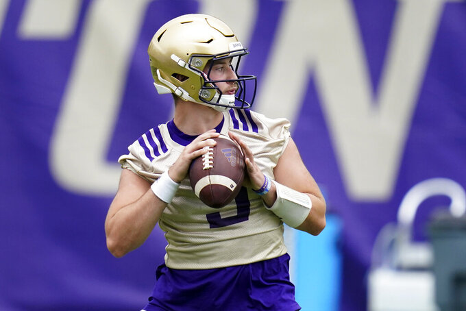 FILE - Washington Huskies quarterback Dylan Morris looks to pass during NCAA college football practice in Seattle, in this Friday, Aug. 6, 2021, file photo. Washington begins the 2021 season as one of the favorites in the Pac-12 North Division, while also trying to erase the bad taste of how last year ended when a COVID-19 outbreak brought a sudden end to an already truncated schedule. (AP Photo/Elaine Thompson, File)