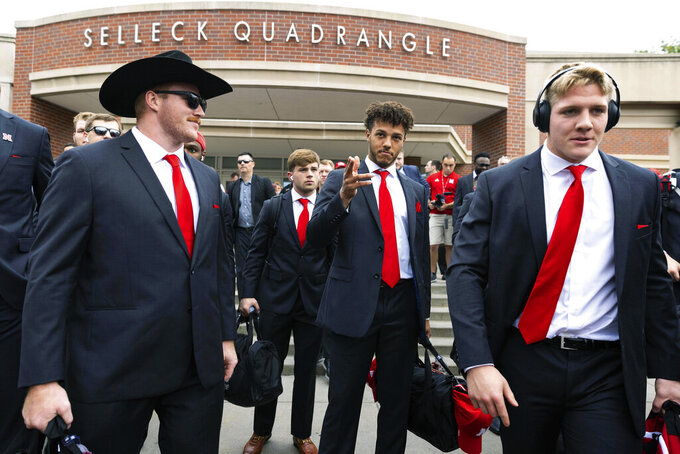 Nebraska quarterback Adrian Martinez, center, signals for his teammates, including offensive lineman Cam Jurgens, left, and linebacker Garrett Nelson, to proceed forward for the Unity Walk from Selleck Quadrangle before an NCAA college football game against Michigan on Saturday, Oct. 9, 2021, in Lincoln, Neb. (AP Photo/Rebecca S. Gratz)