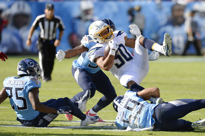Los Angeles Chargers running back Austin Ekeler (30) is stopped by Tennessee Titans inside linebacker Wesley Woodyard (59) in the first half of an NFL football game Sunday, Oct. 20, 2019, in Nashville, Tenn. (AP Photo/Mark Zaleski)