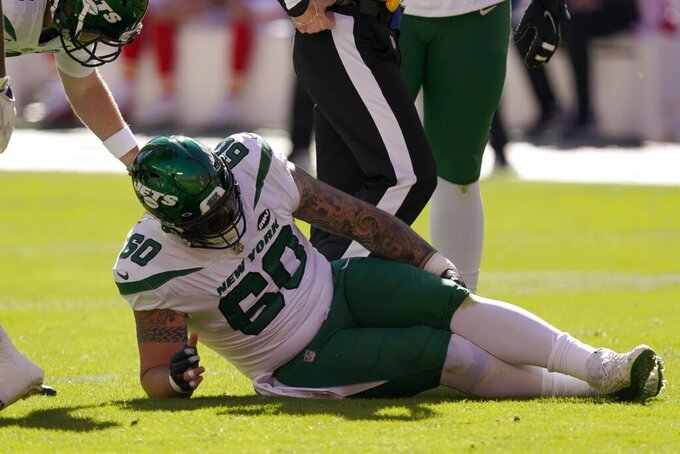 New York Jets center Connor McGovern (60) grabs his leg after suffering an unknown injury in the first half of an NFL football game against the Kansas City Chiefs on Sunday, Nov. 1, 2020, in Kansas City, Mo. (AP Photo/Charlie Riedel)
