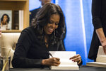 Former first lady Michelle Obama signs copies of her new book