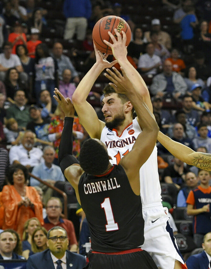 Virginia's Ty Jerome (11) shoots over Gardner-Webb's Jaheam Cornwall (1) during a first-round game in the NCAA men's college basketball tournament in Columbia, S.C., Friday, March 22, 2019. (AP Photo/Richard Shiro)
