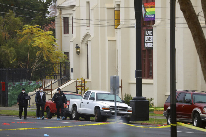 Members of the San Jose Police Department investigate a homicide scene at Grace Baptist Church on Monday, Nov. 23, 2020, in San Jose, Calif. Two people died and multiple others were injured in a stabbing Sunday night at the church, where homeless people had been brought to shelter from the cold weather, police said. (Aric Crabb/Bay Area News Group via AP)