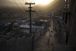 People walk through an alleyway as the sun sets in Kabul, Afghanistan, Thursday, Sept. 16, 2021. (AP Photo/Felipe Dana)