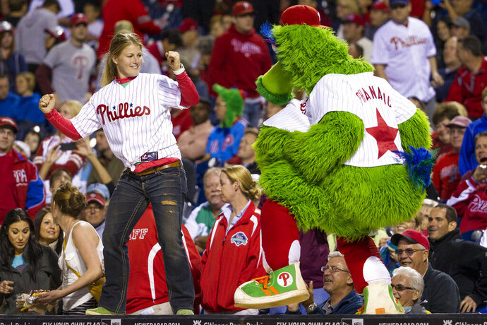 """File-This Sept. 16, 2013. file photo shows the Phillies Phanatic dancing with a fan on the dugout during the eighth inning of a baseball game in Philadelphia. The Philadelphia Phillies have sued the New York company that created the Phanatic mascot to prevent the green fuzzy fan favorite from becoming a free agent. In a complaint filed Friday, Aug. 2, 2019, in U.S. District Court in Manhattan, the team alleged Harrison/Erickson threatened to terminate the Phillies' rights to the Phanatic next year and """"make the Phanatic a free agent"""" unless the team renegotiated its 1984 agreement to acquire the mascot's rights. (AP Photo/Chris Szagola, File)"""