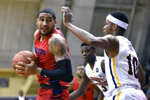 Dayton's Obi Toppin, left, works the ball past La Salle's Isiah Deas during the first half of an NCAA college basketball game, Thursday, Jan. 2, 2020, in Philadelphia. (AP Photo/Derik Hamilton)