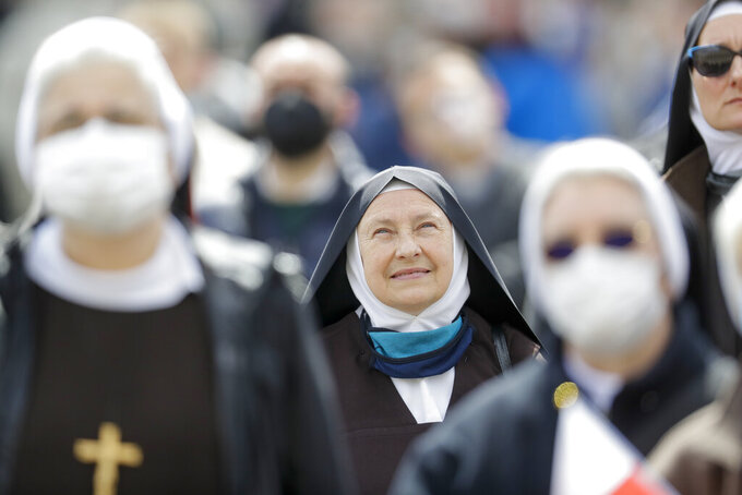 Nuns watch Pope Francis as he recites the Regina Caeli noon prayer from the window of his studio overlooking St.Peter's Square, at the Vatican, Sunday, April 18, 2021. Pope Francis said he is happy to be back greeting the faithful in St. Peter's Square faithful for his traditional Sunday noon blessing after weeks of lockdown measures. (AP Photo/Andrew Medichini)