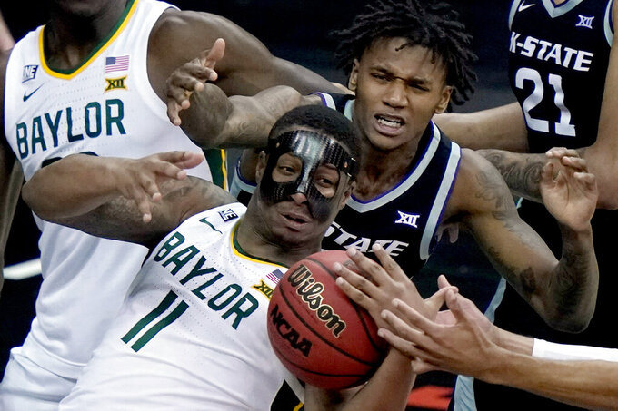 Baylor's Mark Vital (11) and Kansas State's DaJuan Gordon, back, battle for a loose ball during the second half of an NCAA college basketball game in the second round of the Big 12 men's tournament in Kansas City, Mo., Thursday, March 11, 2021. (AP Photo/Charlie Riedel)