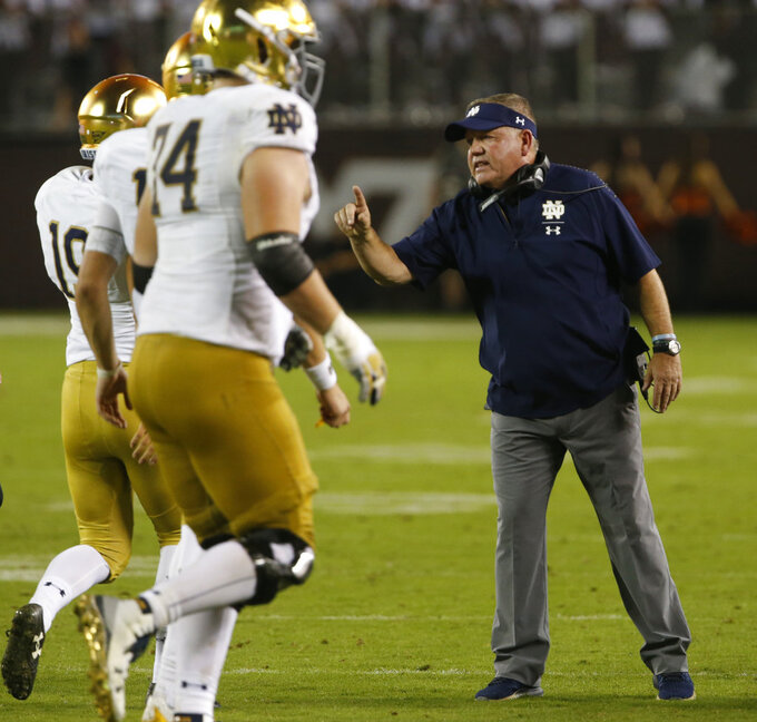 Notre Dame coach Brian Kelly talks to player during the second half of an NCAA college football game against Virginia Tech in Blacksburg, Va., Saturday, Oct. 6, 2018. Notre Dame won 45-23. (AP Photo/Steve Helber)