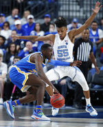 UCLA's Prince Ali (23) drives into North Carolina's Christian Keeling during the first half of an NCAA college basketball game Saturday, Dec. 21, 2019, in Las Vegas. (AP Photo/John Locher)