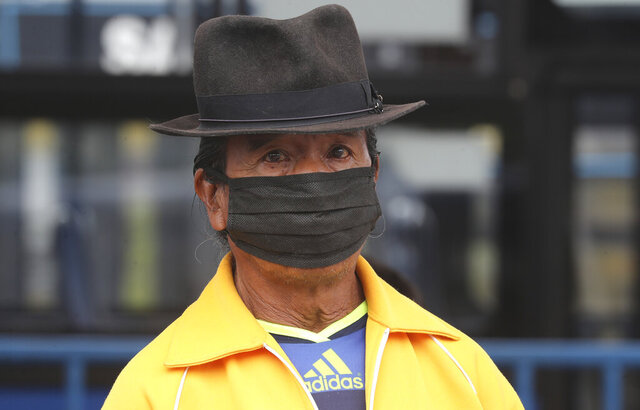 A man, wearing protective face masks as a precaution against the spread of the new coronavirus, waits in a bus line in Quito, Ecuador, Wednesday, June 3, 2020. After 80 days of an almost complete shutdown, the capital city lowers its warning alert from red to yellow allowing for the freer movement of people and the opening of many businesses. (AP Photo/Dolores Ochoa)