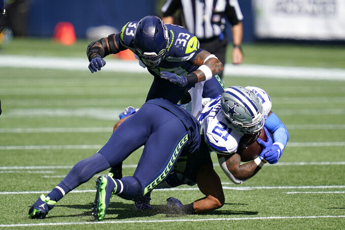 Dallas Cowboys running back Ezekiel Elliott (21) is tackled by Seattle Seahawks middle linebacker Bobby Wagner and strong safety Jamal Adams (33) during the first half of an NFL football game, Sunday, Sept. 27, 2020, in Seattle. (AP Photo/Elaine Thompson)