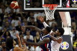 France's Mathias Lessort, center keeps the ball from United States' Marcus Smart at right during a quarterfinal match for the FIBA Basketball World Cup in Dongguan in southern China's Guangdong province on Wednesday, Sept. 11, 2019. France defeated United States 89-79. (AP Photo/Ng Han Guan)