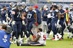 Houston Texans nose tackle Brandon Dunn (92) sits on the field as Tennessee Titans players celebrate after the Titans won 42-36 in overtime at an NFL football game Sunday, Oct. 18, 2020, in Nashville, Tenn. (AP Photo/Mark Zaleski)