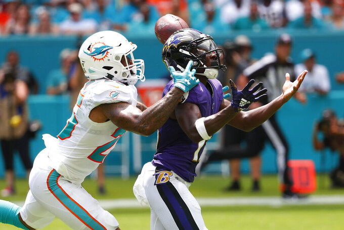 Miami Dolphins cornerback Xavien Howard (25) attempts to catch intended for Baltimore Ravens wide receiver Marquise Brown (15), during the first half at an NFL football game, Sunday, Sept. 8, 2019, in Miami Gardens, Fla. (AP Photo/Wilfredo Lee)