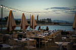 A couple have dinner in an empty restaurant next to the beach in Barcelona, Spain, Wednesday Sept. 23, 2020. Spain is struggling to contain a second wave of the virus which has killed at least 30,000 people according to the country's health ministry. (AP Photo/Emilio Morenatti)