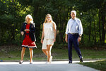 Former Vice President and Democratic presidential candidate Joe Biden, his wife Jill, left, and their granddaughter Finnegan, center, arrive at a house party at former Agriculture Secretary Tom Vilsack's house, Monday, July 15, 2019, in Waukee, Iowa. (AP Photo/Charlie Neibergall)
