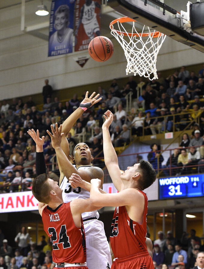 Wofford forward Cameron Jackson (33) shoots for the basket between Virginia Military forward Will Miller (24) and forward Tyler Creammer (25) in the first half of an NCAA college basketball game in the Southern Conference tournament championship, Saturday, March 9, 2018, in Asheville, N.C. (AP Photo/Kathy Kmonicek