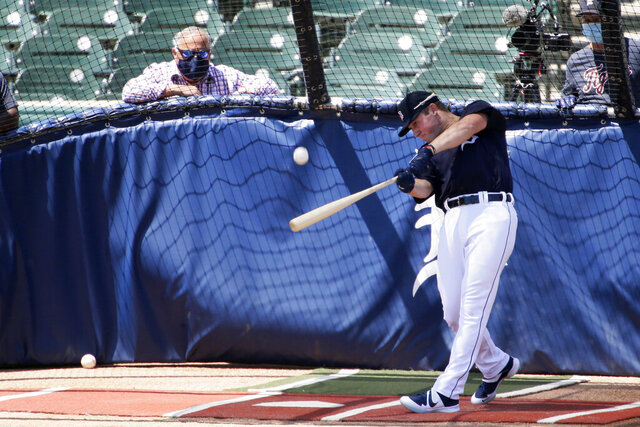 Detroit Tigers' Spencer Torkelson hits in the batting cage as Tigers general manager Al Avila, left, watches during baseball training camp at Comerica Park Saturday, July 4, 2020, in Detroit. (AP Photo/Duane Burleson)
