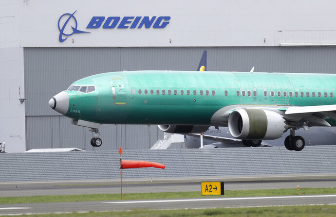 FILE - In this April 10, 2019, file photo a Boeing 737 MAX 8 airplane being built for India-based Jet Airways lands following a test flight at Boeing Field in Seattle. Boeing Co. reports earnings Wednesday, April 24. (AP Photo/Ted S. Warren, File)
