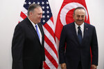 U.S. Secretary of State Mike Pompeo, left, shakes hands with Turkey's Foreign Minister Mevlut Cavusoglu before their meeting during a NATO Foreign Ministers meeting at the NATO headquarters in Brussels, Wednesday, Nov. 20, 2019. (AP Photo/Francisco Seco, Pool)