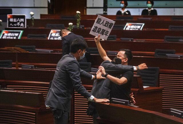 Pan-democratic legislator Chan Chi-chuen holding a placard reading