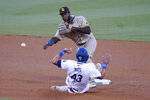 San Diego Padres second baseman Jurickson Profar, top, completes a double play over Los Angeles Dodgers' Edwin Rios on a ground ball by Will Smith during the third inning of a baseball game Wednesday, Aug. 12, 2020, in Los Angeles. (AP Photo/Marcio Jose Sanchez)