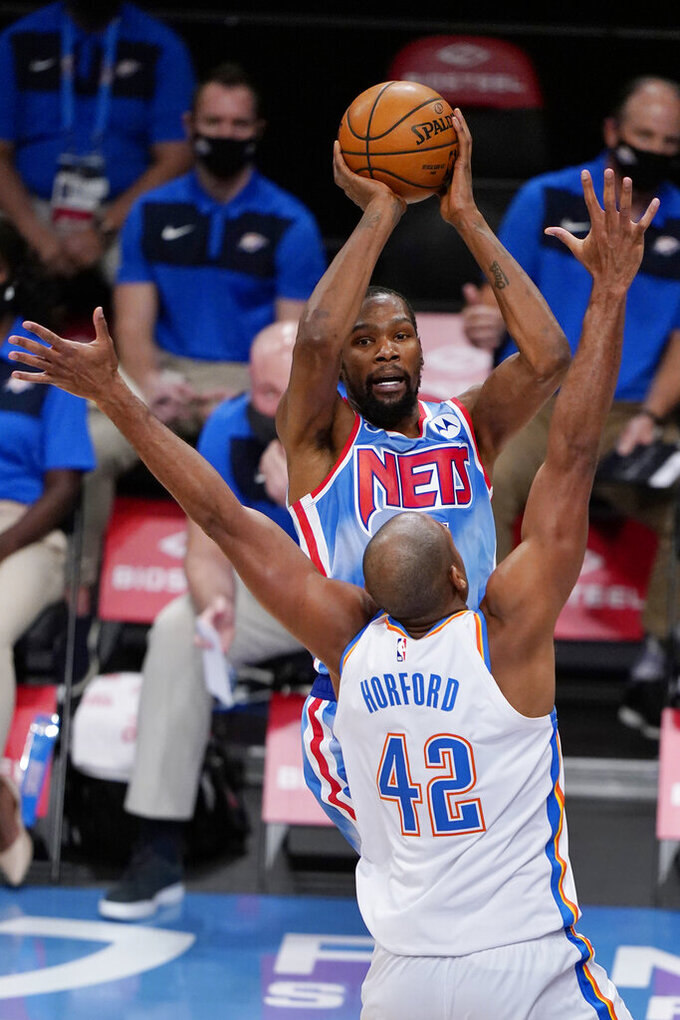 Brooklyn Nets forward Kevin Durant (7) looks to pass over Oklahoma City Thunder center Al Horford (42) during the second half of an NBA basketball game Sunday, Jan. 10, 2021, in New York. (AP Photo/Kathy Willens)